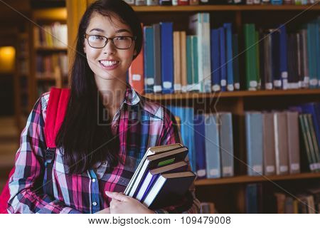 Smiling student holding a book in the library at the university