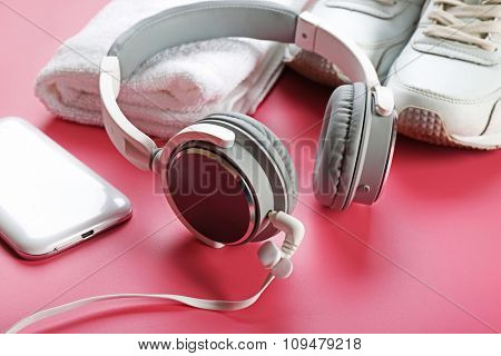 Headphones and sport equipment on pink background