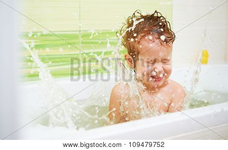 Happy Baby Child Bathes In A Bath Sprinkles And Plays With The Foam And Bubbles