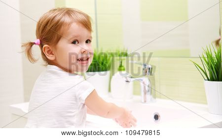 Child Little Girl Washes Her Hands In Bathroom