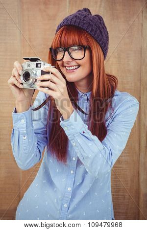Smiling hipster woman taking pictures with a retro camera against wooden background