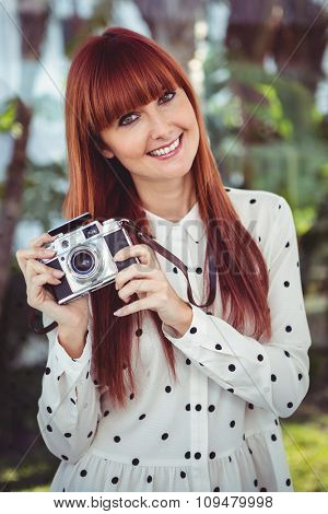 Attractive smiling hipster woman with old fashioned camera in the garden