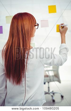 Attractive hipster woman writing on sticky notes in her office