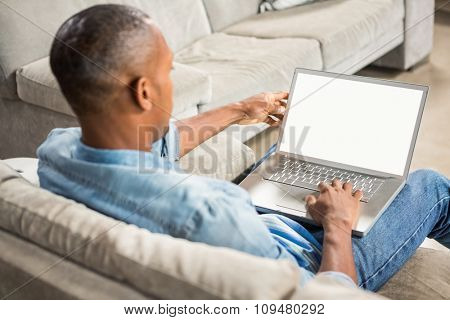 Over shoulder view of casual man using laptop in living room