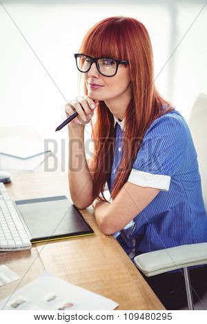 Attractive hipster woman thinking in her office