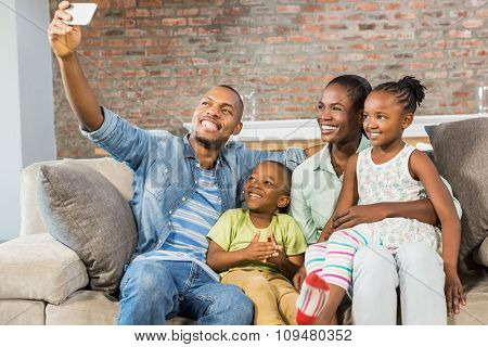 Happy family taking a selfie on the couch in living room