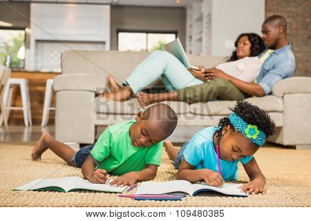 Happy siblings on the floor drawing in the living room