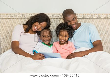 Family with digital tablet in bed at home