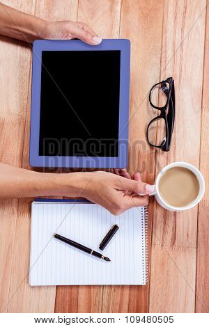 Overhead of feminine hands using tablet with coffee, notebook and glasses on desk