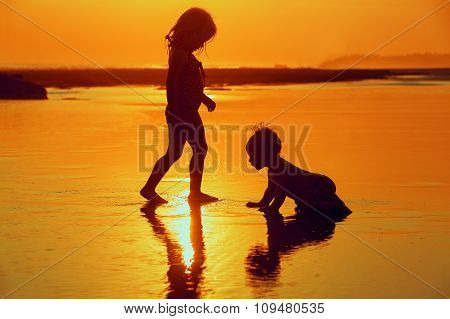 Children Playing With Fun On The Sunset Sea Beach