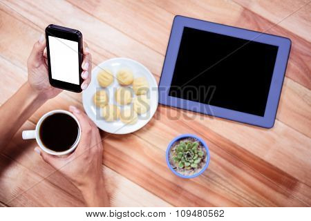 Overhead of feminine hands holding smartphone and coffee with tablet and biscuits on desk