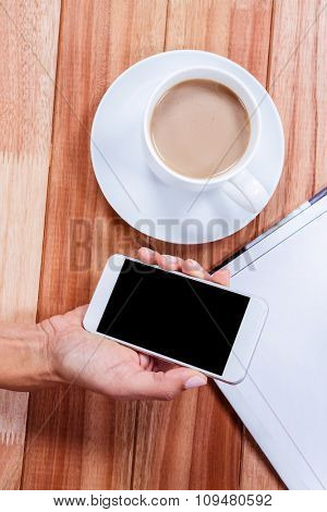 Part of hand holding smartphone on wooden desk