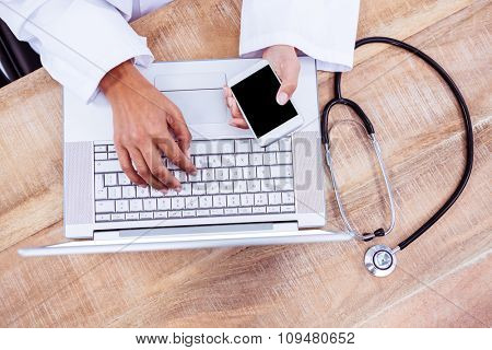 Doctor using smartphone on wooden desk at work