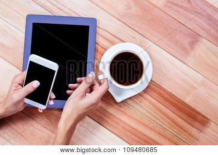 Businesswoman holding smartphone and coffee cup at work