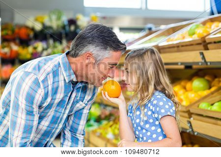 Cute girl holding an orange to her father at the grocery shop