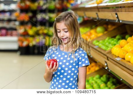Cute kid in the supermarket looking at an apple