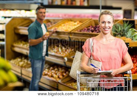 Smiling woman holding the grocery list at the supermarket