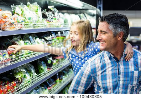Daughter staying on her fathers back and buying vegetables