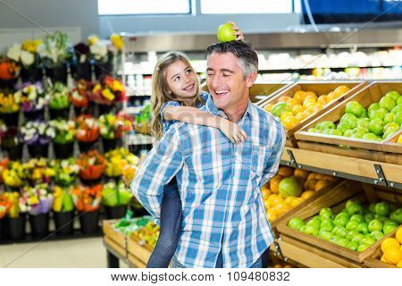 Father giving his daughter a piggy back at supermarket