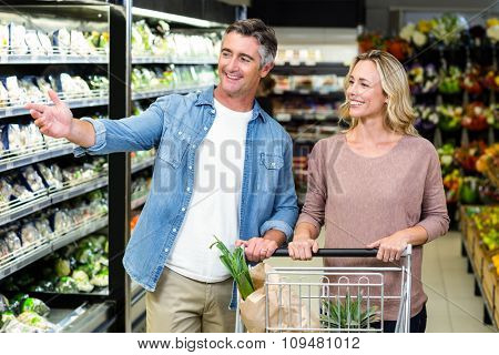 Smiling couple buying food products in supermarket