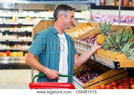 Smiling man choosing pineapple at supermarket
