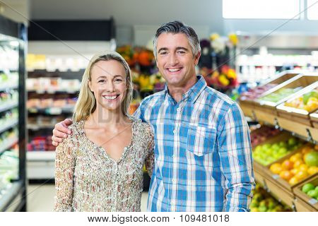Portrait of smiling bright couple at supermarket