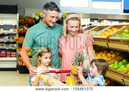 Young family behind their trolley at supermarket