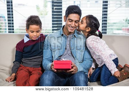 Happy father receiving a gift from his children in living room