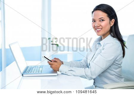 Smiling businesswoman using smartphone at the desk in work