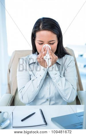 Businesswoman blowing her nose at the desk in work