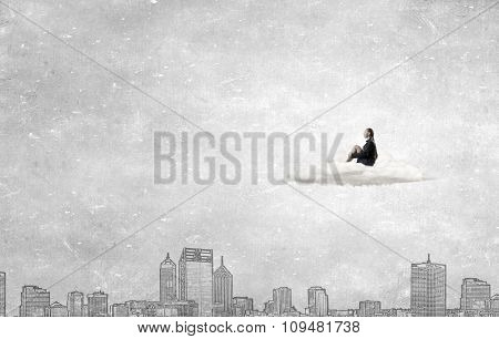 Thoughtful young businesswoman sitting alone on cloud above city