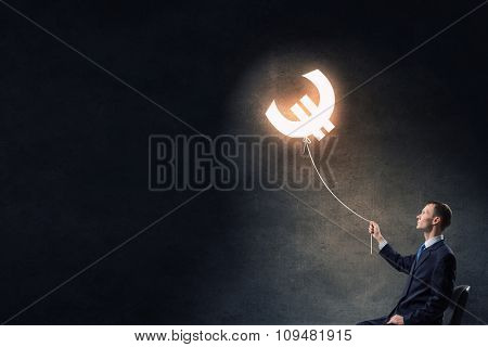 Businessman catching glowing euro currency symbol with rope
