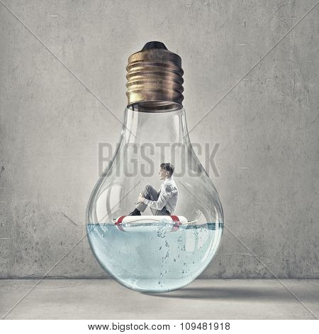 Young businessman floating on life buoy inside of light bulb