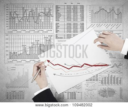 Businessman hands writing with pen infographs on paper