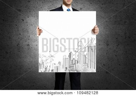 Businessman holding banner with urban construction concept