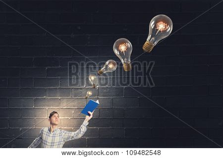 Businessman holding opened book and glass light bulbs flying out