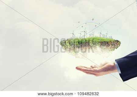 Hands holding eco concept with windmill generators