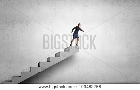 Young businesswoman running up staircase representing success concept
