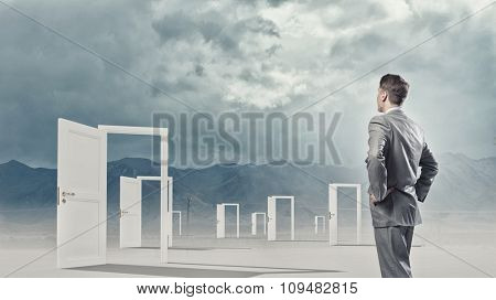 Businessman standing in front of opened doors and making decision