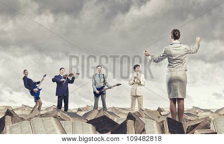 Conductor hand and business people playing different music instruments