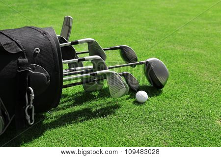 Golf bag with clubs and balls on green field, close up