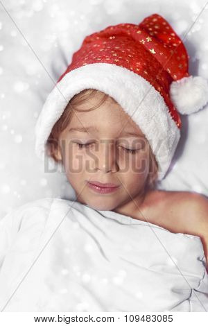 Boy in Santa hat sleeping on a pillow
