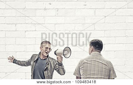 Young man in casual screaming aggressively in megaphone on adult man