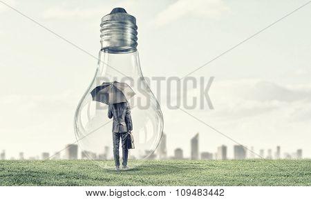 Businessman with umbrella and briefcase inside light bulb