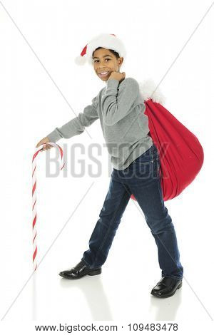 A handsome elementary boy wearing a Santa hat with Santa's sack over his shoulder and a giant candy cane leading his way.  On a white background.