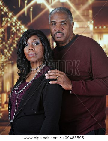 A serious, mature African American couple posing at nighttime outside a Christmas-lit mall.