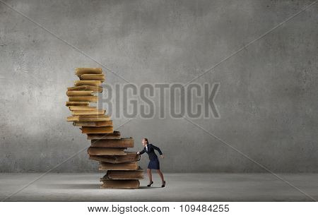 Determined businesswoman climbing up pile of books