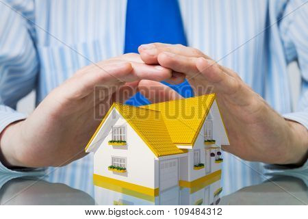 Hands of businessman covering house model with care