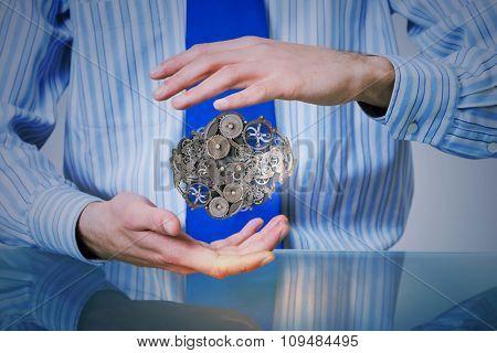 Businessperson holding gears and cogwheels mechanism in hands