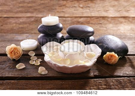 Spa composition of stones, candles and a rose on wooden table